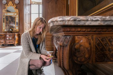 Rian Haarhuis bij meubel in de grote zaal van kasteel Cannenburch