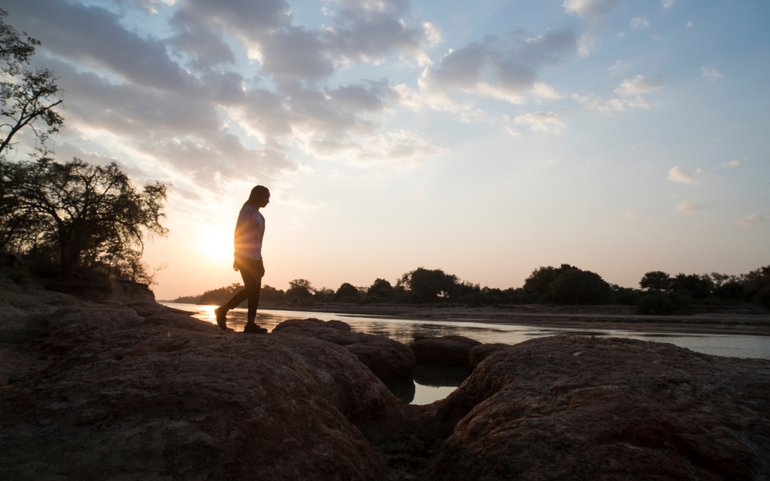 Agness walking next to the Luangwa river at sunset
