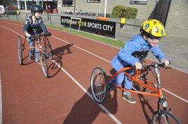 Twee kinderen op driewielers op eeen renbaan