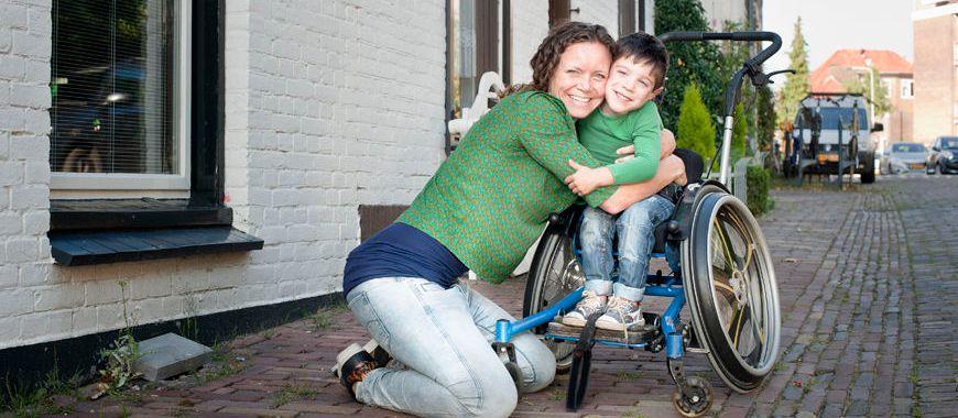 Vrouw omhelst jongen in rolstoel
