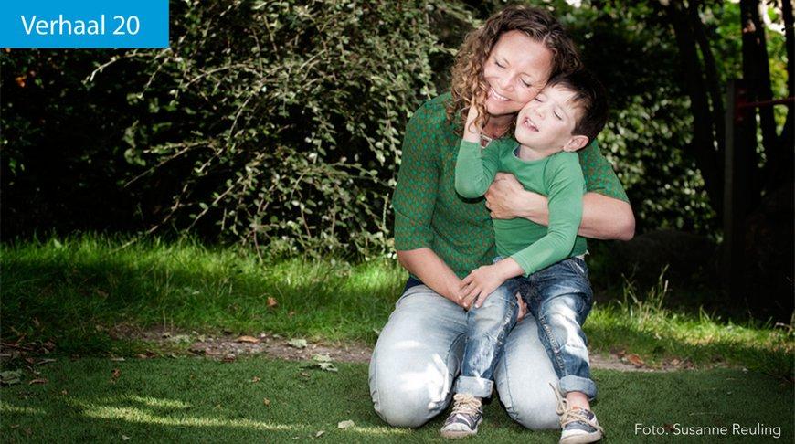 Vrouw zit met jongetje op haar schoot in het gras